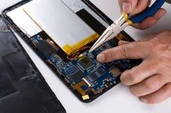 Persona que usa las herramientas para reparar el dispositivo electrónico Imágenes de archivo libres de regalías