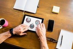 Persona que usa una tableta con los iconos de la educación en la pantalla Imagen de archivo