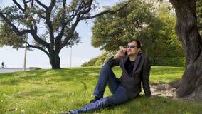 Persona relajada del negocio que se sienta en hierba verde cerca del árbol, hablando en smartphone almacen de metraje de vídeo