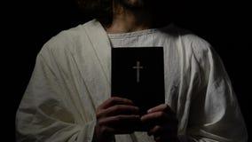 Persona religiosa en Sagrada Biblia de la tenencia del traje cerca del corazón, iglesia cristiana, fe almacen de metraje de vídeo