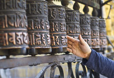 Persona sconosciuta che fila le ruote di preghiera buddisti Fotografie Stock Libere da Diritti