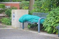 Persona sin hogar en banco de la ciudad Imagen de archivo