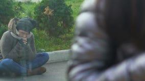 Persona sin hogar pobre que se sienta cerca del café, de la gente de observación comiendo y riendo almacen de video