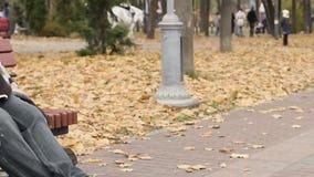 Persona sin hogar pobre que se sienta en banco con la muestra hambrienta, pidiendo dinero suelto almacen de metraje de vídeo