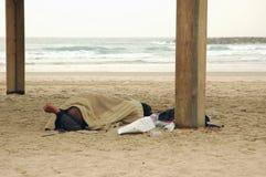 Persona sin hogar que duerme en la playa Imagen de archivo libre de regalías
