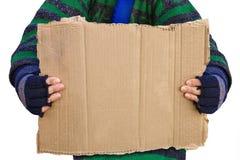 Persona sin hogar que lleva a cabo a un tablero en blanco Fotos de archivo libres de regalías