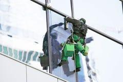 Persona som reparerara kyrktorn tvättar fönster av ett höghus Arkivbilder