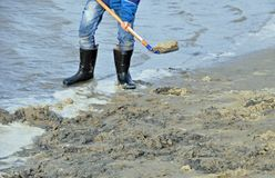 Persona in stivali di gomma sulla spiaggia Fotografie Stock Libere da Diritti