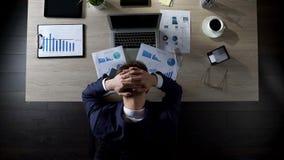 Persona trastornada del negocio que se sienta en la oficina y que piensa en las deudas, quiebra fotografía de archivo libre de regalías