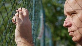 Persona triste y del trastorno que mira de detrás una cerca metálica imagen de archivo libre de regalías