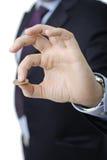 Persona in un vestito che tiene una moneta Immagini Stock Libere da Diritti