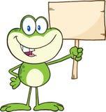 Personaggio dei cartoni animati sveglio della rana verde che ostacola un segno di legno Fotografie Stock