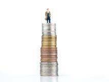 Personaje de dibujos animados del negocio que se coloca en moneda del metal Imagen de archivo