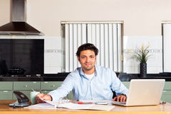 Personal administration. Handsome man doing his personal administration, such as taxes, paying bills and checking his finances at a kitchen table Royalty Free Stock Image
