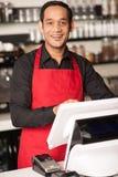 Personal alegre del barista en el contador de efectivo imágenes de archivo libres de regalías