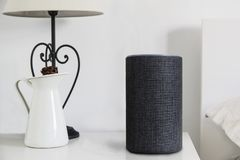 Personal assistant connected loudspeaker on a wooden table in a Smart Home in a bedroom. Next, lamp and a jar. Copy space for Editor`s text royalty free stock photo