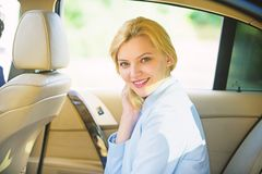 Personal assistant and driver. Business life concept. Business woman sit on backseat. Busy lady passenger leather car. Salon enjoy journey with chauffeur stock photo