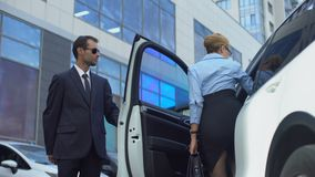 Personal assistant of female politician opening car door to his boss, service. Stock footage stock footage
