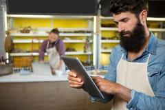 Personal atento que usa la tableta digital en el contador de la panadería foto de archivo