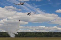 Personal av departementet av nöd- lägen som besprutar vatten över träd på helikoptrar MI-8 och MI-26 under flygsporthändelse Royaltyfria Foton