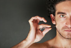 Personal care - man pulling his beard with tweezers Royalty Free Stock Photos