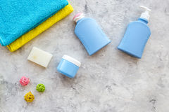 Personal care. Towels, soap and shampoo, cream on grey stone backgrond top view copyspace Stock Images