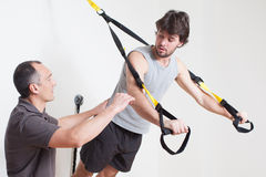 Personal coach explaining suspension training Stock Images