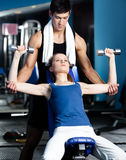 Personal coach helps woman to exercise with weights Stock Photography