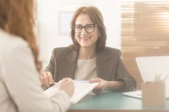 Personal coach presenting counseling services. Happy personal coach presenting counseling services to a corporate employee royalty free stock image