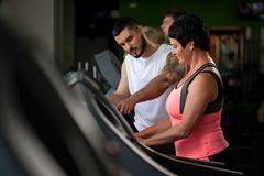 Personal coach talking with female client in gym Royalty Free Stock Photo