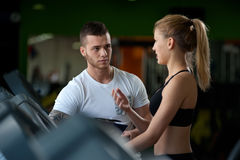 Personal coach talking with female client in gym. Male personal trainer talking with female client in gym. Attractive blonde women working out on treadmill with stock image