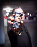 Personal communication. Mand holding phone at camera with his own face in the display Royalty Free Stock Image