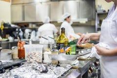 Personal de la cocina ocupado con la preparación de la comida en restaurante de lujo imagenes de archivo