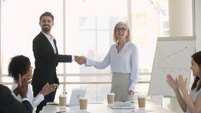 Personal de la compañía que aplaude mientras que apretones de manos de saludo del director con el nuevo empleado almacen de metraje de vídeo