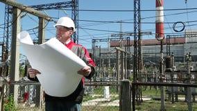 Personal de mantenimiento con los dibujos de funcionamiento en la central nuclear metrajes