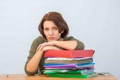 Personal de oficina de la muchacha que se inclina cuidadosamente en una pila de carpetas Fotos de archivo