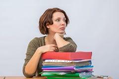 Personal de oficina de la muchacha que se inclina cuidadosamente en una pila de carpetas Imágenes de archivo libres de regalías