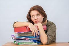 Personal de oficina de la muchacha que se inclina cuidadosamente en una pila de carpetas Foto de archivo