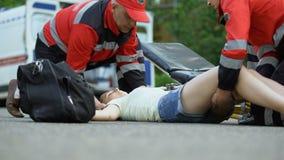 Personal de servicio de ambulancia que lleva a la muchacha inconsciente a la ambulancia, usando ensanchador metrajes