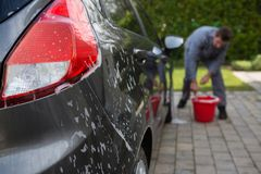 Personal de servicio auto que lava un coche imagenes de archivo