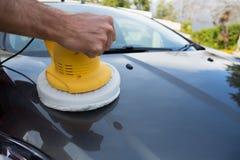 Personal de servicio auto que limpia un capo del coche con el cepillo giratorio del lavado foto de archivo libre de regalías