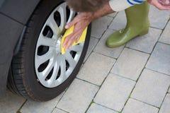 Personal de servicio auto que limpia un neumático con el plumero imagenes de archivo