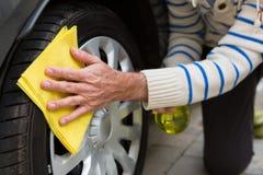 Personal de servicio auto que limpia un neumático con el plumero foto de archivo libre de regalías