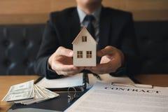 Personal de ventas de las propiedades inmobiliarias dar el hogar artificial a los clientes foto de archivo libre de regalías