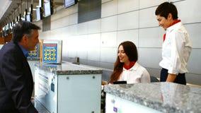 Personal del aeropuerto de dos hembras que comprueba el pasaporte y que obra recíprocamente con el hombre en el mostrador de fact almacen de metraje de vídeo