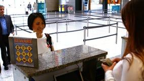 Personal del aeropuerto de dos hembras que comprueba el pasaporte y que obra recíprocamente con los viajeros en el mostrador de f almacen de metraje de vídeo