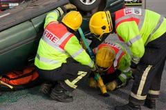 Personal del fuego y del rescate en el entrenamiento del choque de coche Fotografía de archivo
