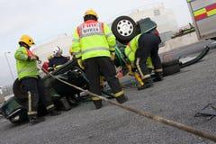Personal del fuego y del rescate en el entrenamiento del choque de coche Foto de archivo