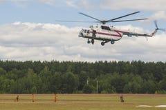 Personal des Ministeriums der Notsituationen, die Wasser über Bäumen auf MI-8MT Hubschrauber sprühen lizenzfreie stockfotografie