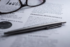 Personal development in a business text with glasses and a pen. Personal development highlighted in a educational text with glasses and a pen Royalty Free Stock Photo